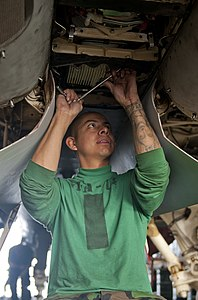 US Navy 111228-N-OY799-048 Aviation Machinist's Mate 3rd Class Felix Cadena, from Los Angeles, installs an auxiliary power unit on an F-A-18E Super.jpg