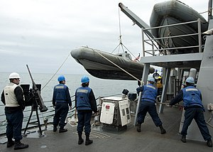 US Navy 120118-N-NL401-020 Sailors lower a rigid-hull inflatable boat to be used during a visit, board, search and seizure exercise aboard the Arle.jpg