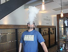 E-cigarette user blowing a cloud of vapor.