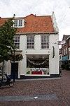 foto van Hoekpand Hoogstraat. Gotisch huis, gedekt door zadeldak, aan de Zuidzijde afgesloten door een trapgevel met ezelsrugafdekkingen. Aan de Marktzijde schuiframen in stijl 18e eeuw