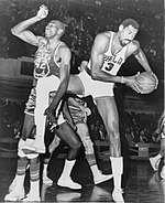 "A basketball player, wearing a jersey with the word ""PHILA"" and the number 13, is holding a basketball while another basketball player, wearing a jersey with the word ""RIP CITY"" and the number 42, is standing next to him."