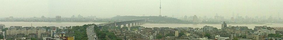 Panorama of Wuhan as viewed from the Yellow Crane Tower.Left to right: Yangtze River, Wuchang, Wuhan Yangtze River Bridge, Hanyang Tortoise Mountain TV Tower, mouth of the Han River and Hankou.