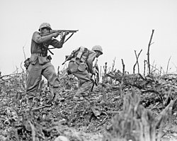 a black and white image of two Marines in their combat uniforms. One Marine is providing cover fire with his M1 Thompson submachinegun as the other with a Browning Automatic Rifle, prepares to break cover to move to a different position. There are bare sticks and rocks on the ground.