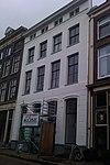 foto van Huis met schilddak en geel gepleisterde lijstgevel met in de verdieping oorspronkelijke schuiframen