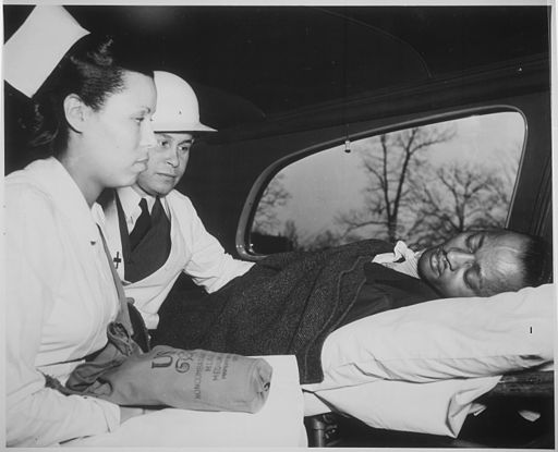 """After receiving first aid treatment in practice raid in Washington, DC, air-raid `victim' is removed to hospital by a M - NARA - 535826"