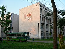 Semplice edificio in cemento, con un autobus verde all'esterno