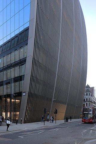 photo: The curved profile of the new office building at 70 St Mary Axe, vertical fins defining the side which runs along the road Bevis Marks, along which are seen pedestrians and a red bus.