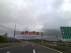 Variable traffic signs placed on a gantry spanning three motorway traffic lanes, indicating slippery pavement and reduced speed limit