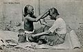 A Tamil barber dressing a man's hair in a street. Photograph Wellcome V0019800.jpg