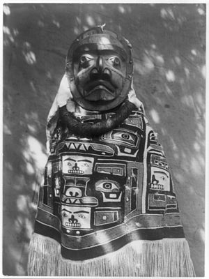 Kwagu'ł - Kwagu'ł woman wearing a fringed Chilkat blanket (worn backwards), a hamatsa neckring and mask representing a deceased relative who had been a shaman. Photograph by Edward S. Curtis c. 1883.