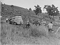 A group of men hauling a stuck and badly damaged automobile on a hillside (AM 77683-1).jpg