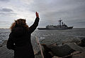 A woman waves to the guided missile frigate USS Taylor (FFG 50) as it leaves Naval Station Mayport, Fla., Jan. 8, 2014, for a seven-month deployment to the U.S. 5th and 6th Fleet areas of responsibility 140108-N-MJ645-076.jpg