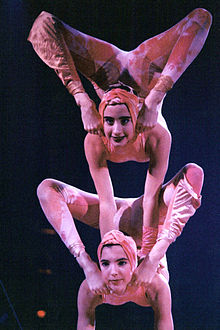 A female acrobat balancing on top of another.
