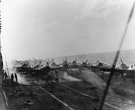 View of the flight deck of Lexington, at about 15:00 on 8 May. The ship's air group is spotted aft, with Wildcat fighters nearest the camera. Dauntless dive bombers and Devastator torpedo bombers are parked further aft. Smoke is rising around the aft aircraft elevator from fires burning in the hangar. Aircraft sit on the smoldering flight deck of USS Lexington (CV-2) during the Battle of the Coral Sea, 8 May 1942 (80-G-16802).jpg