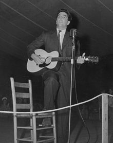 Lomax playing guitar on stage at the Mountain Music Festival, Asheville, North Carolina, in the early 1940s.
