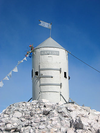 Aljaž Tower - Aljaž Tower. Two inscriptions are visible: Aljažev stolp on the tower, and 1895, the year of construction, on the flag