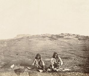 Zuni - Zuni men and the ancient Pueblo Town of Zuni, ca.1868