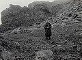 Antakelig Elen Olsen i samisk drakt, stående i fjellandskap i Båtsfjord, med ljå i hendene - Norsk folkemuseum - NF.13322-008.jpg