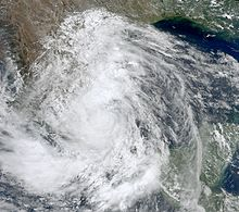 A satellite image of a large, swirling mass of clouds making landfall in Mexico