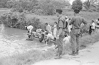 Communist insurgency in Sarawak - Armed soldiers guarding a group of Chinese villagers who were taking a communal bath in 1965 to prevent them from collaborating with the Communist guerillas and to protect the area from Indonesian infiltrators.