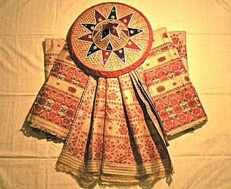 Assam silk - A set of mekhela chadors made with Muga silk from Assam arranged around a Jaapi and set on a shawl made with Eri silk.