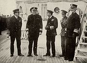 Five men, all in immaculate naval dress, stand on deck.