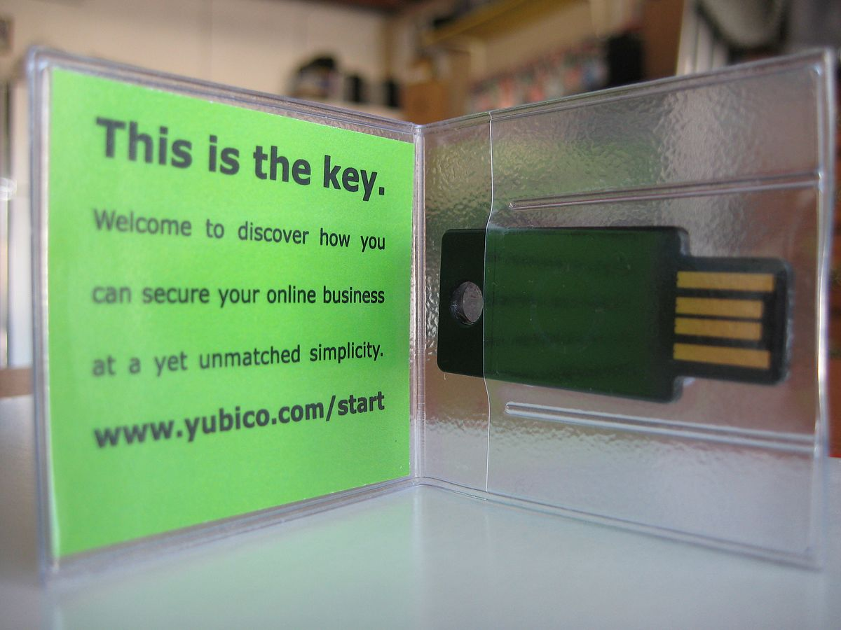 A YubiKey in its holder, along with an instruction card describing its use.