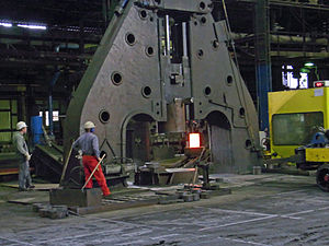 Forging - Hot metal ingot being loaded into a hammer forge