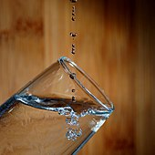 Water dripping into a glass, showing drops and bubbles.