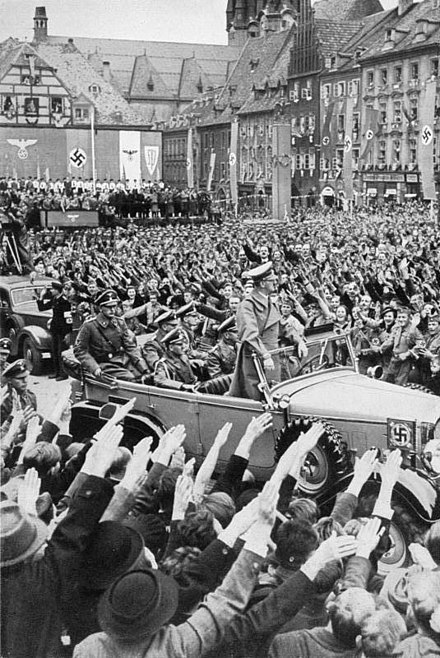 October 1938: Hitler is driven through the crowd in Cheb (German: Eger ), in the mostly German-populated Sudetenland region of Czechoslovakia, which had been annexed to Nazi Germany as part of the Munich Agreement Bundesarchiv Bild 137-004055, Eger, Besuch Adolf Hitlers.jpg