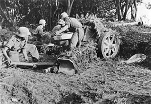 German soldiers in uniform with helmets, serving as crew of an anti-tank gun