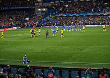 Chelsea (blue) and Barcelona players (yellow) leave the pitch at the end of the first half of their semi-final second leg at Stamford Bridge. The referee is talking to two Barcelona players.