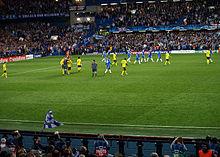 Les joueurs de Chelsea (bleu) et de Barcelone (jaune) quittent le terrain à la fin de la première moitié de leur demi-finale retour à Stamford Bridge.  L'arbitre parle à deux joueurs de Barcelone.