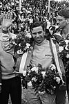 Jim Clark waving the camera in celebrating winning a race