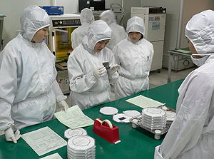 Cleanroom suit - Technicians wearing clean room suits inspect a semiconductor wafer