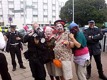 Three protesters dressed as clowns posing with a FIT photographer. Other officers are stood around smiling