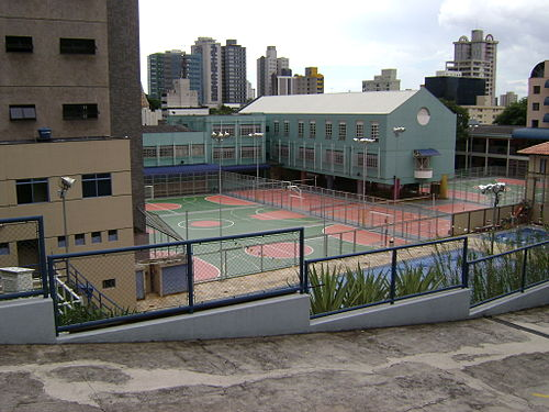 A sport club in Belo Horizonte, Brazil, showing various paved and painted surfaces for futsal, basketball and volleyball, with two swimming pools in the foreground. Clube.JPG