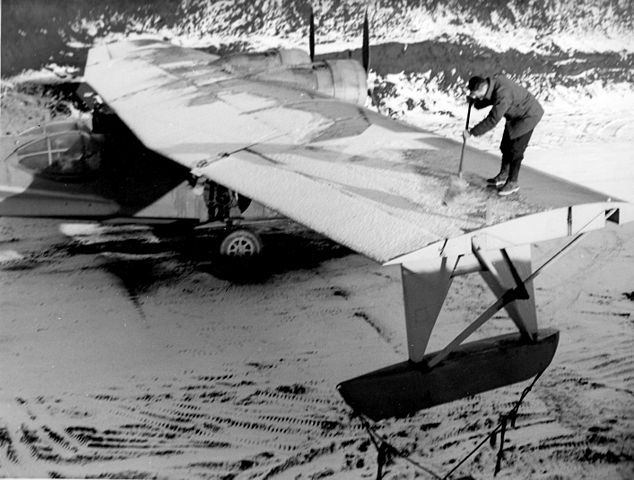 A U.S. Navy ground crew member removes the snow from a Consolidated PBY-5A Catalina at an Alaskan base, circa in 1943.