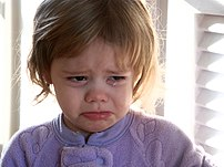 A toddler girl crying