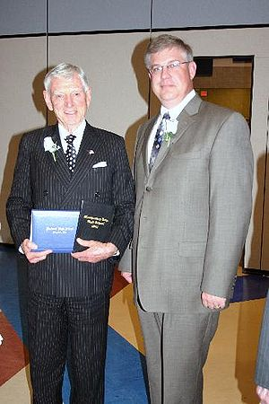 David H. Murdock (left) receiving the high school diploma he didn't get. He has in his hands the diplomas from he should have graduated and the 2009 diploma. Next to him is the the high school principal..