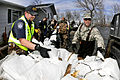 Defense.gov News Photo 110429-F-WA217-326 - U.S. Air Force Tech. Sgt. Tracy Winterquist right and Ryan Latozke left unload sandbags to create a barrier blocking rising overland flood water.jpg