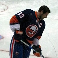 "Doug Weight standing against the rink boards, wearing the captain's ""C"" on his jersey."