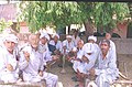 Elderly voters showing their voters's identity card gather under a tree after casting their votes at a polling booth of Sonepat in Haryana on May 10, 2004.jpg