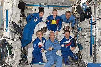 Flight suit - Expedition 21 crew members pose with three Extravehicular Mobility Unit (EMU) spacesuits in the Columbus laboratory of the International Space Station.