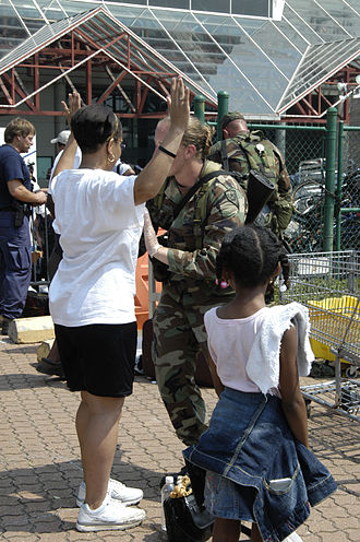 Frisking - An evacuee is frisked before being airlifted out of New Orleans after Hurricane Katrina.