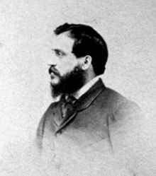 A head-and-shoulders photograph of Beato in profile. He is facing towards the left of the frame and has a full beard.