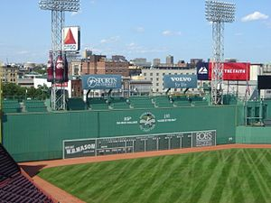The bottom of the picture shows part of the orange clay colored warning track at Fenway Park.