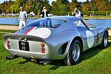 Rear view of a silver sports car parked on grass facing a river
