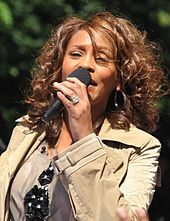 A picture of a woman with brown curly hair wearing a jacket, singing