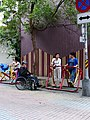 Foreign Workers Talking at Lane with Elder Man in Wheelchair 20130427.jpg